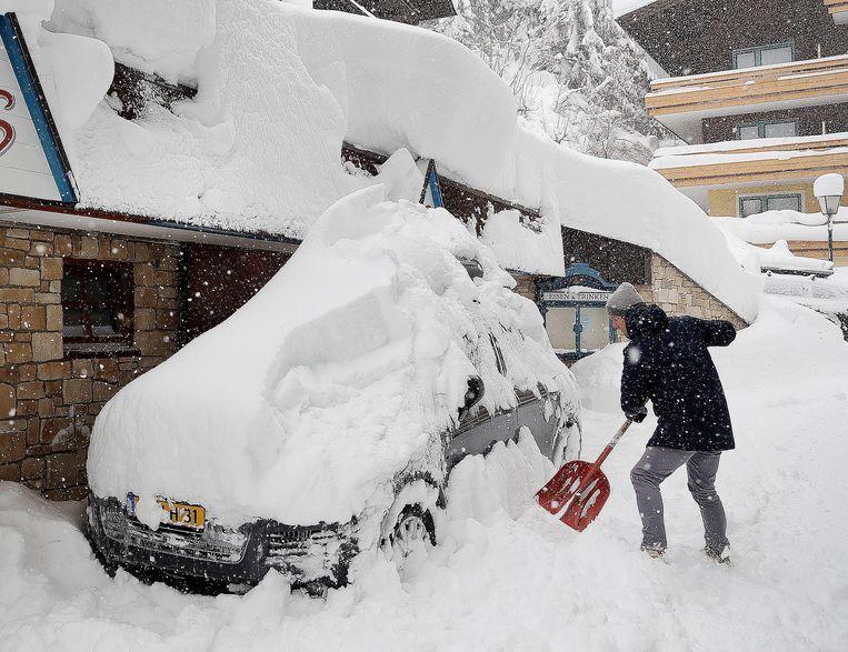 Een toerist probeert zijn auto sneeuwvrij te maken in  Filzmoos. Beeld AP