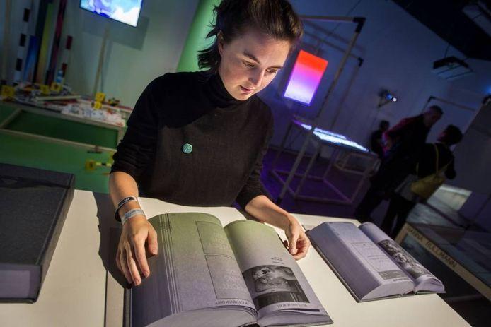 Dieuwertje Luitse toont het door haar gemaakte boek dat op de DDW deel uitmaakt van de expositie In Real Life van ArtEZ. Het geeft de reacties op sociale media weer op een kunstwerk Frank Benson.
