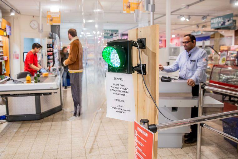 Eigenaar Nawin Harpal van supermarkt MCW Utrecht heeft een stoplicht opgehangen om te zorgen dat er niet teveel klanten in zijn winkel zijn. Om besmetting met het coronavirus te voorkomen mogen winkels een beperkt aantal klanten tegelijk toelaten. Beeld ANP