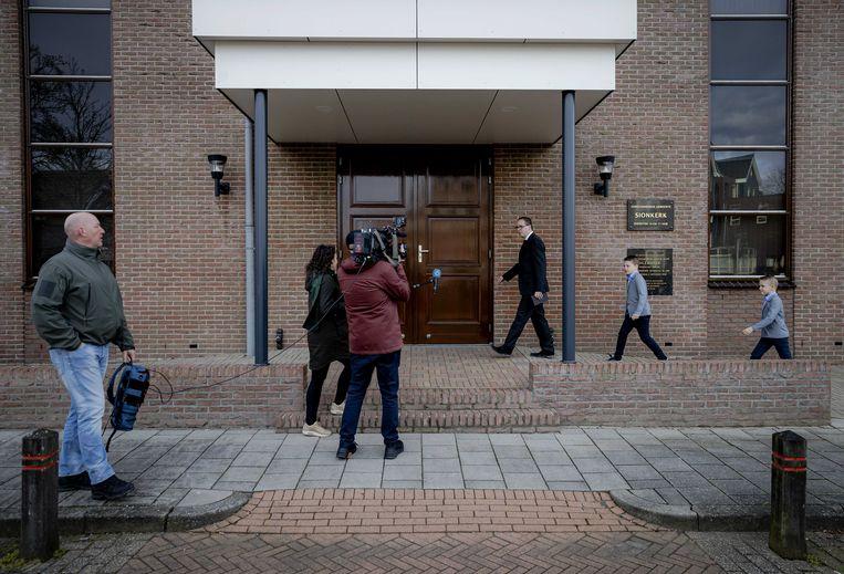 Kerkgangers betreden de Sionkerk op Urk. De kerk gooide zondag de deuren open voor een groter publiek, tegen de coronamaatregelen in. Beeld ANP
