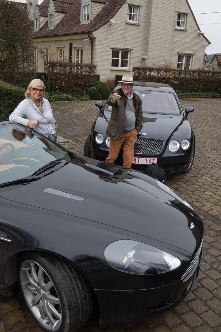 Willy en Marie-Jeanne bij hun Aston Martin (voorgrond) en Bentley. De sleutels die ze hier ophouden, geven ze een weekend lang aan vijf werknemers.