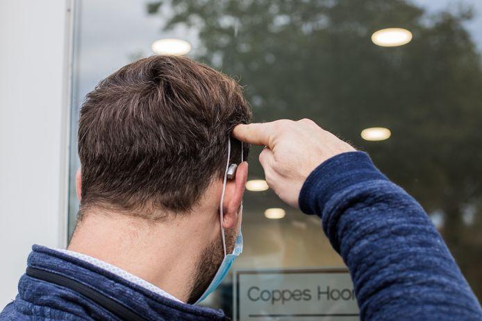 Jochem Coppes uit Groesbeek demonstreert de methode om een mondkapje af te doen.