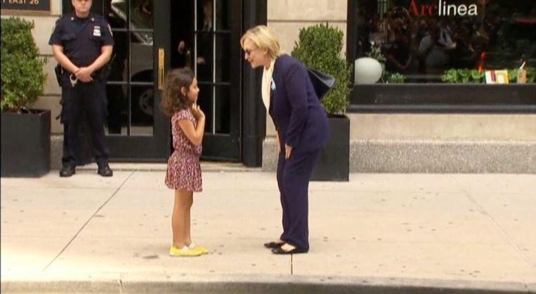 Clinton begroet een meisje op straat nadat ze het appartement van haar dochter heeft verlaten. Beeld reuters