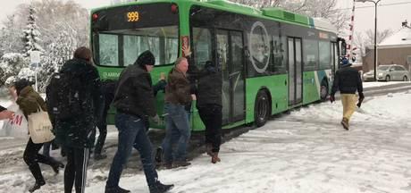 Passagiers helpen bus verder door de sneeuw