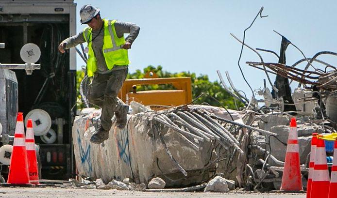 Een reddingsmedewerker springt van de ruïnes af.