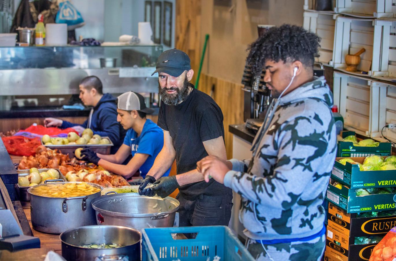Vrijwilligers bereiden de maaltijden voor in restaurant Uno aan de Stationsweg.