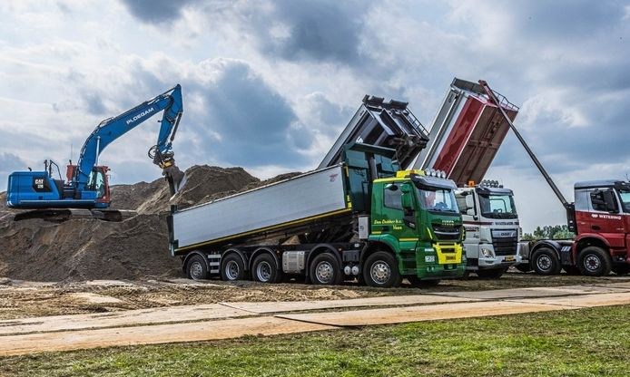 Vrachtwagens worden vol zand geladen zodat eventuele wellen, zoals in Doeveren, kunnen worden gedicht.