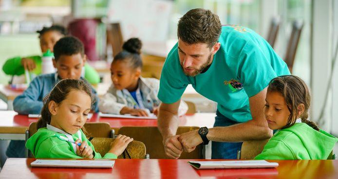 Meester Joris probeert basisschoolleerlingen verder te helpen tijdens een zomerschool in Rotterdam. Hamide (links) luistert aandachtig.