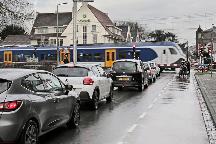 Wachtende automobilisten voor de spoorwegovergang aan de Molenstraat in Oss. Een spoortunnel zou oplossing kunnen bieden, maar kost vele miljoenen.