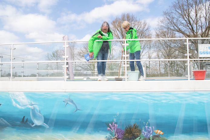 Anneke Ruitenberg (links) en Alice Zandman maken het hekwerk rond het zwembad schoon. Openluchtzwembad Olde Vechte gaat volgende week zaterdag om 14.00 uur open.