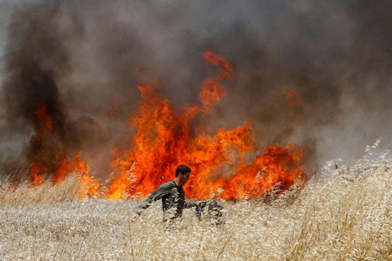 Een Israëlische soldaat probeert een brand te blussen veroorzaakt door aan vliegers gebonden brandbommen. Beeld AFP