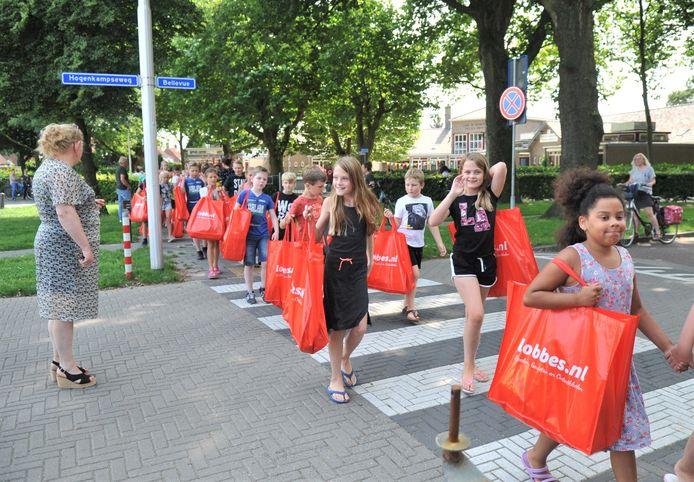 Kinderen van de Beatrixschool met de gevulde tassen op weg naar de Albert Schweitzerschool.