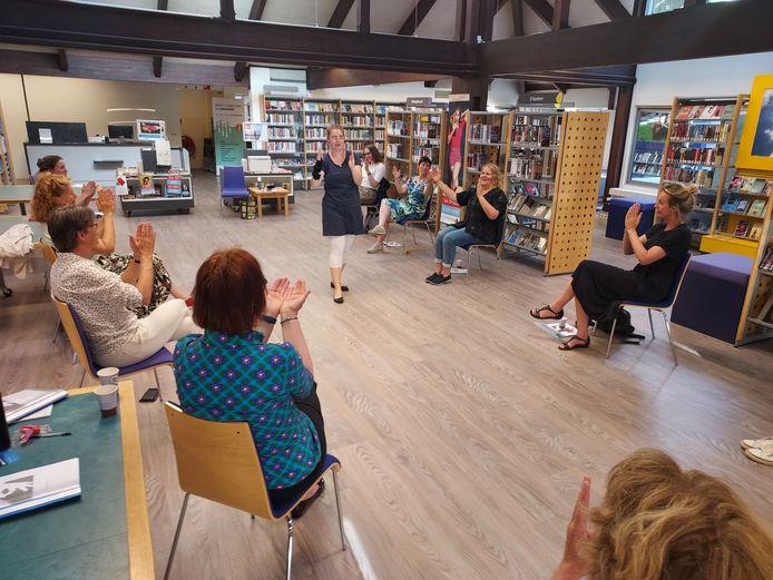 Femke Keupink oefent gebaren met medewerkers van de Bibliotheek Oost-Achterhoek.