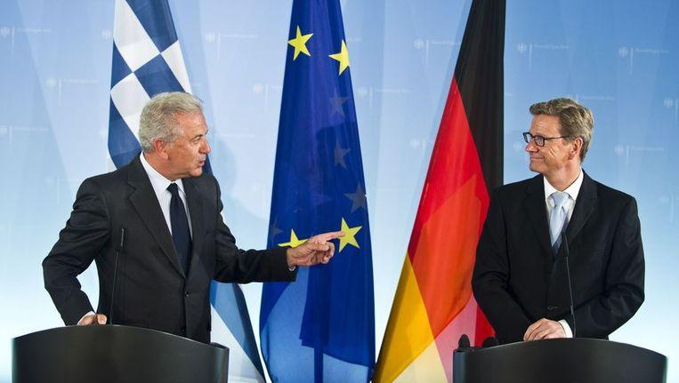 Duits minister van Buitenlandse Zaken Guido Westerwelle (rechts) en zijn Griekse collega Dimitris Avramopoulos op een personferentie in Berlijn aan de vooravond van de gesprekken tussen Merkel en Samaras. Beeld AFP
