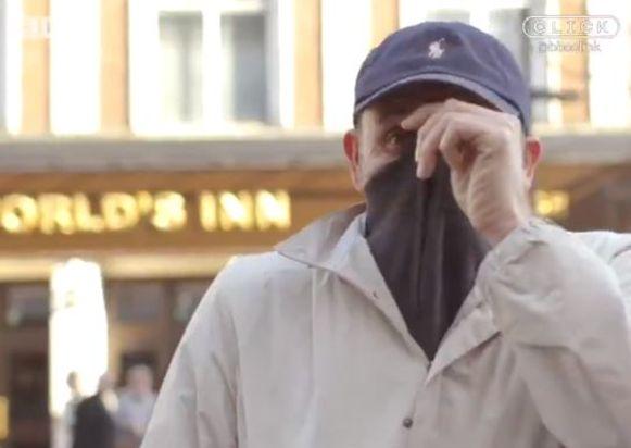De voorbijganger verborg zijn gezicht in zijn trui.