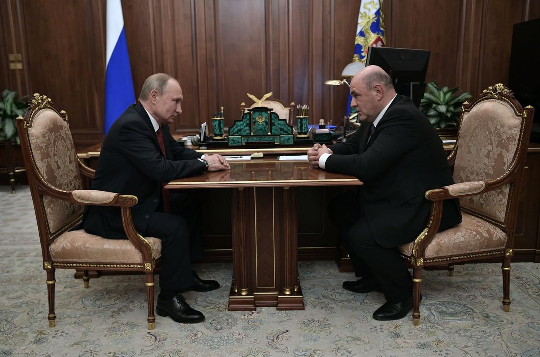 Poetin ontmoet belastingchef Michaïl Misjoestin, voordat hij diens benoeming als premier bekendmaakt.  Beeld AFP