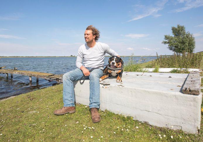 Bastiaan van 't Westeinde met hond Luna op de plek aan het Veerse Meer waar hij z'n ecolodges wil bouwen.