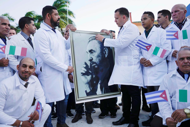 Cubaanse dokters nemen afscheid in Havana, voordat ze op coronamissie gaan naar Italië.  Beeld REUTERS