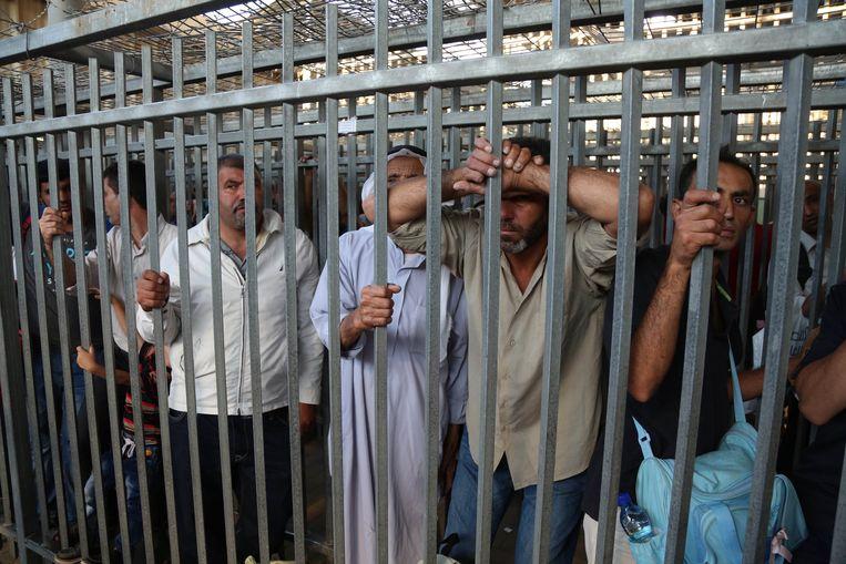 Palestijnse arbeiders wachten aan de Qalandia-checkpoint om Israël binnen te mogen. Maar de checkpoints gaan vaak te laat open, waardoor ze riskeren te laat op hun werk aan te komen. Beeld Anadolu Agency