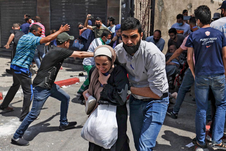 Palestijnen in Gaza-stad vluchten weg na een nieuwe luchtaanval van Israël. Beeld AFP