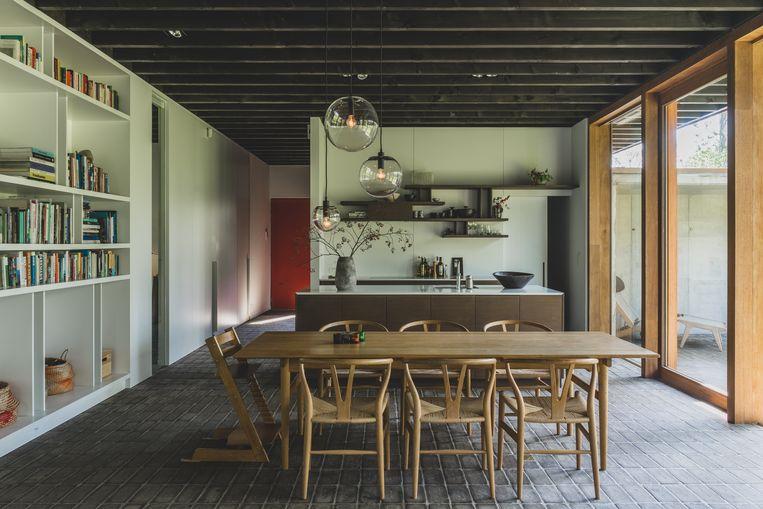 Een van de weinige kleuraccenten in de woning is de rode voordeur. Voor de inrichting kozen Peter en Alexandra voor sobere designklassiekers zoals deze tafel en stoelen van Hans Wegner.  Beeld Hannelore Veelaert