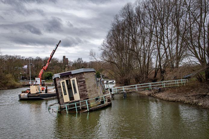 De woonboot wordt door een ponton tegen gehouden.