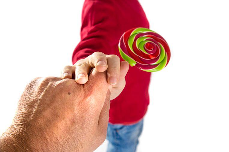 Een man probeert een kind met een snoepje mee te lokken.
