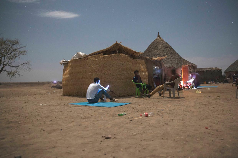 Ethiopische vluchtelingen net over de grens in Soedan zoeken naar een netwerk met hun mobiele telefoons.