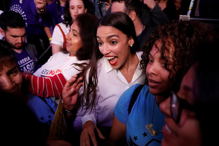 De Democrate Alexandria Ocasio-Cortez uit New York, die behoort tot de linkervleugel van de partij, groet aanhangers tijdens een feest in New York.   Beeld REUTERS