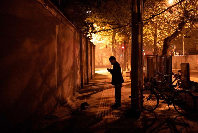 Een inwoner van Wuhan in gebed. Beeld AFP