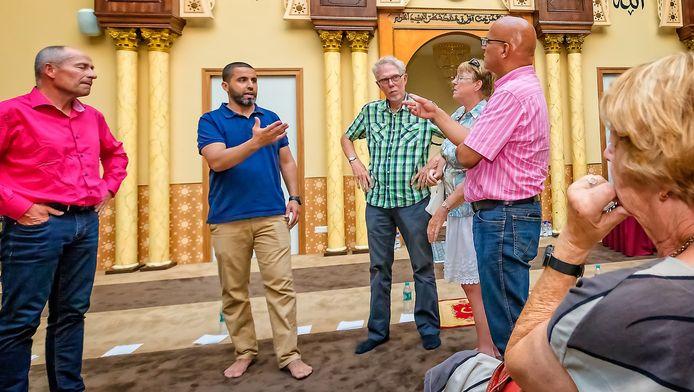 Rachid Oucharia (blauw shirt) leidt de bewoners rond in de Imam Malik moskee.