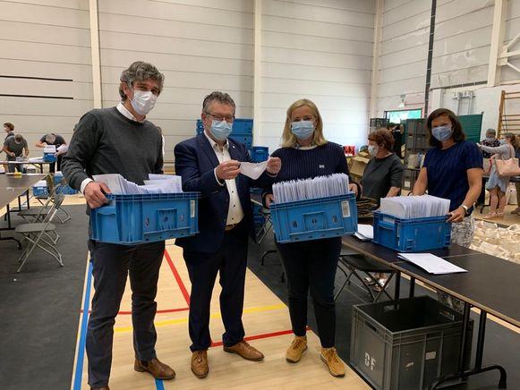 Burgemeester Dirk De fauw (tweede van links) toont, in het bijzijn van collega Martine Matthys en enkele personeelsleden, hoe het mondmasker eruit ziet.