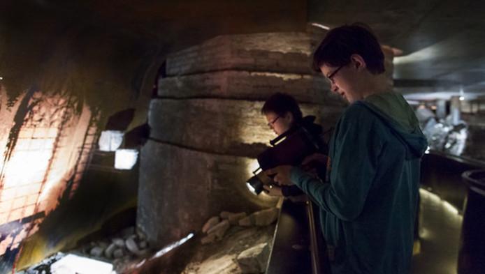 Bezoekers van DomUnder kijken met een speciale zaklamp rond in het ondergrondse museum. DomUnder trok tot nog toe bijna 30.000 bezoekers.