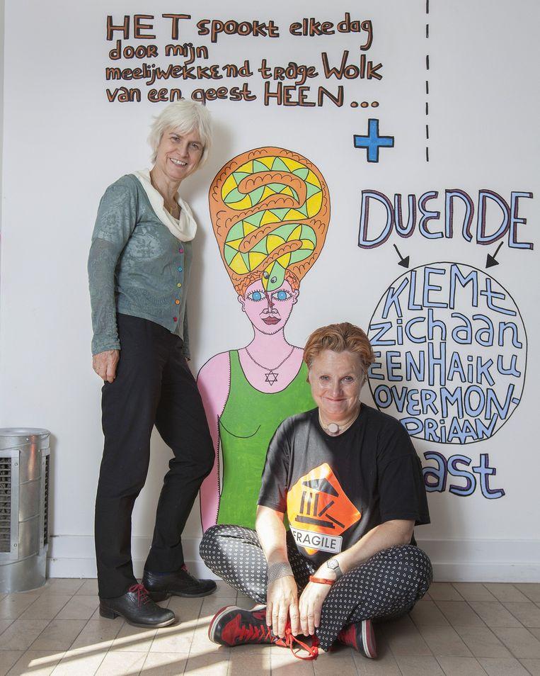 Marli Huijer (links) en Pam Emmerik in de Espressobar van Boijmans Van Beuningen, tegen de achtergrond van muurschilderingen van Pam Emmerik. Beeld Maartje Geels
