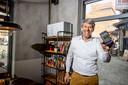 Otomat-eigenaar Bernard Sironval toont de app op zijn smartphone die aangeeft hoe het gesteld is met de luchtkwaliteit in zijn restaurant. Op het rek achteraan staat een compacte luchtreiniger van Genano.