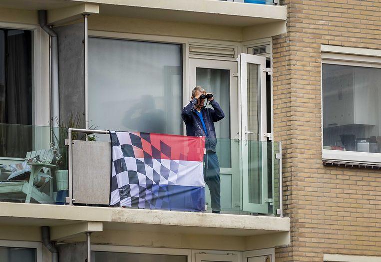 Een bewoner kijkt vanaf zijn balkon richting Circuit Zandvoort. Van de rechter mag daar komend weekend de Dutch Grand Prix Zandvoort worden verreden. Beeld ANP