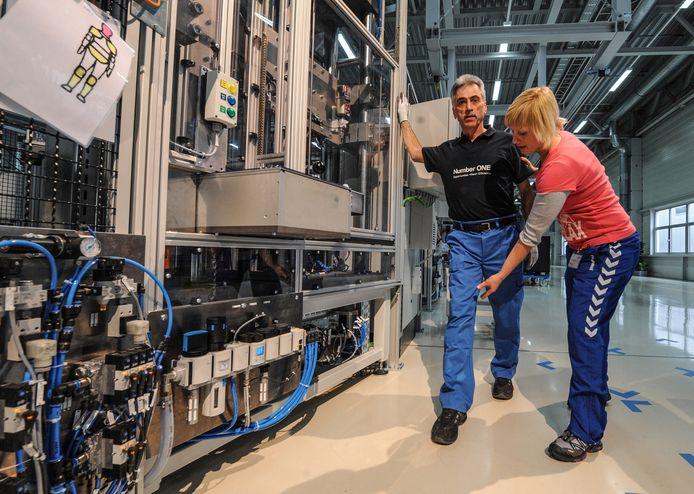 Een fysiotherapeut laat een oudere werknemer bij BMW in Dingolfing (Duitsland) ontspanningsoefeningen doen.