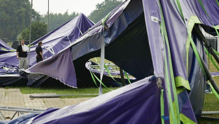 Op het terrein van het festival Zwarte Cross in Lichtenvoorde vielen vier gewonden toen windhozen podiumtenten die werden opgezet, omver bliezen.Twee tentenbouwers nemen de schade op. Een van de bouwers raakte bij het noodweer gewond. Foto ANP Beeld ANP