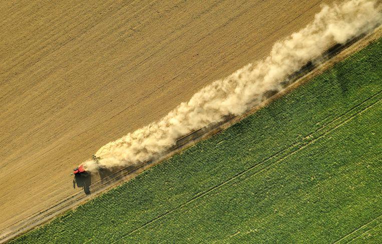 Een Franse boer, aan werk op zijn land, werpt een stofwolk op.  Beeld Reuters