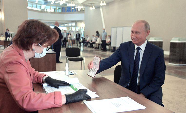 Russisch president Vladimir Poetin toont zijn paspoort bij een stemming over een wijziging van de grondwet. Beeld EPA