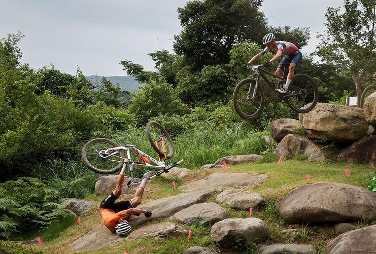 Mathieu van der Poel  gaat onderuit op de plek waar de mountainbikers met hun fiets een sprong moeten maken en belandt daarbij hard op zijn heup.  Beeld REUTERS