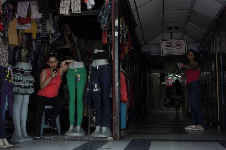 Een vrouw kijkt op haar telefoon en wacht op klanten in San Cristobal. Beeld REUTERS