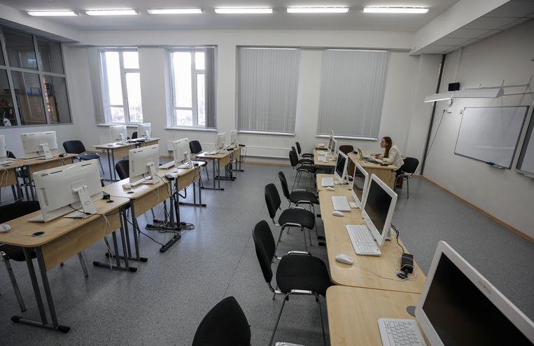 Een leraar geeft online les in een leeg klaslokaal in Moskou.   Beeld EPA