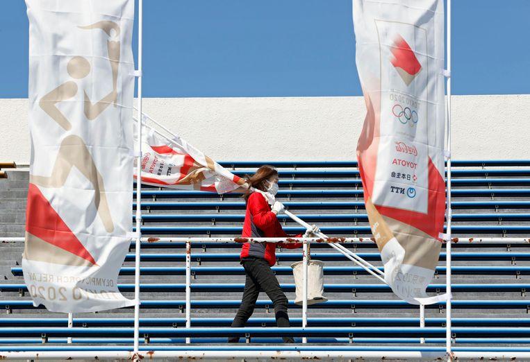 Ter voorbereiding van de Olympische fakkeltocht in Iwaki, Fukushima, worden vlaggen neergezet. Beeld AP