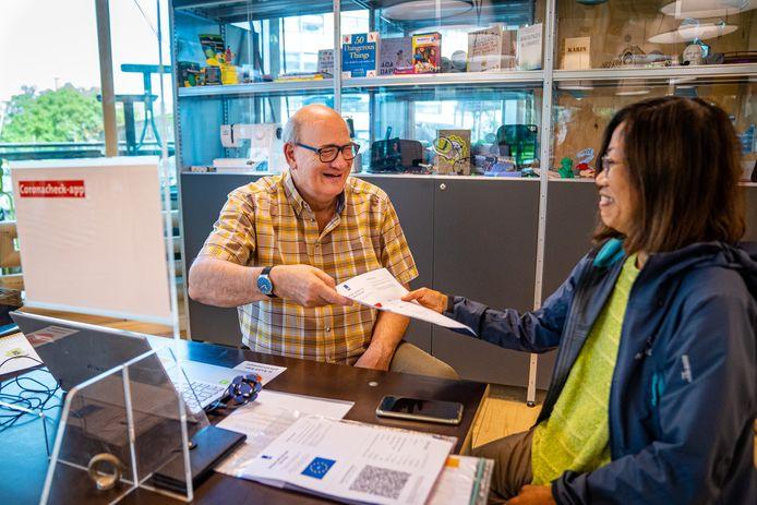 Weer iemand blij. André Rommers, vrijwilliger bij de Centrale Bibliotheek, reikt een uitgeprinte QR-code uit.