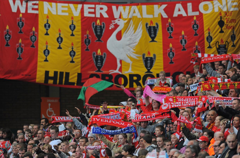 Liverpool-supporters zingen 'You'll Never Walk Alone' om de verjaardag te herdenken van de Hillsborough-ramp (15 april 1989). Het nummer is het lijflied en motto van de club maar wordt ook veel ruimer erkend en gespeeld om zijn verbindende boodschap. Beeld Hollandse Hoogte / AFP