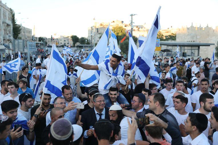 Betogers verzamelen zich rond de ultranationalistische parlementariër Itamar Ben Gvir tijdens de protestmars. Beeld EPA