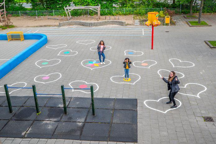 Hartjes op het schoolplein van de Laurentiusschool SBO Delft. Juf Jennifer en de leerlingen Rose-Elle (midden) en Dangerelle oefenen alvast 'de anderhalve meter'.