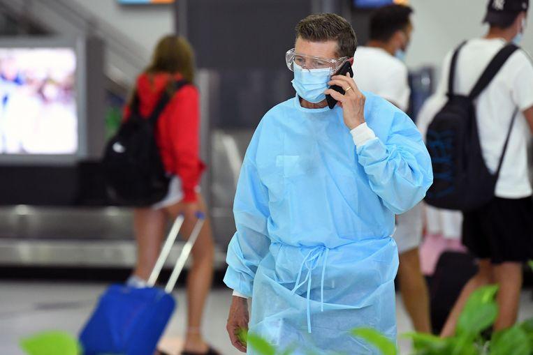 Archiefbeeld: man met beschermende kledij op Australische luchthaven. Beeld EPA