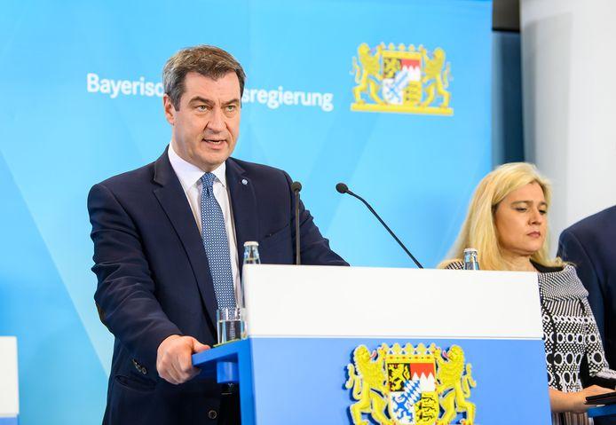 Minister-president Markus Söder (L) van de deelstaat Beieren en Gezondheidsminister Melanie Huml tijdens het afkondigen van de verscherpte maatregelen, vanmiddag.